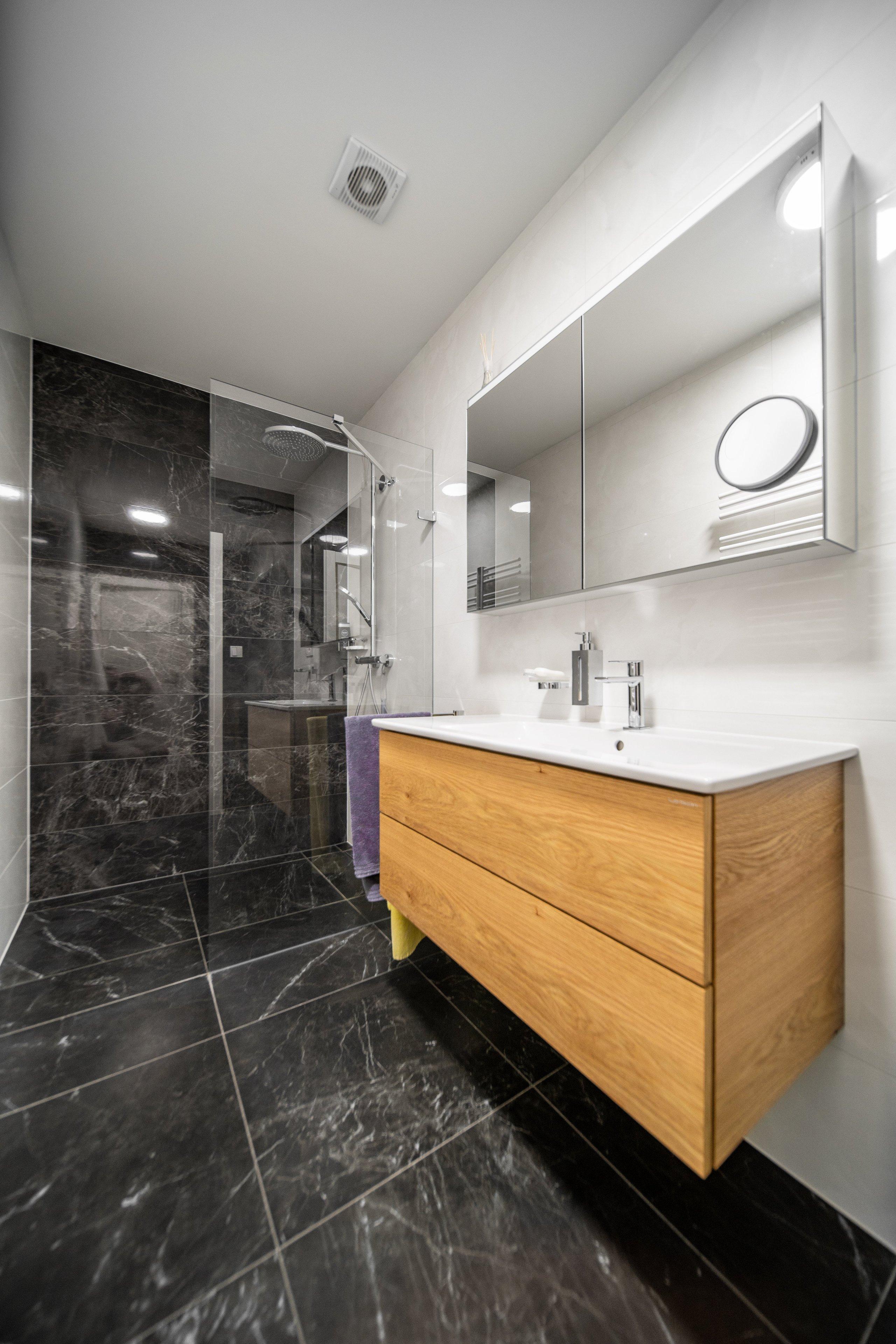 Moderní byt pro manželský pár, který miluje umění. Bytem se prolíná kontrast bílé a antracitu s doplňujícím dubem a betonovými prvky.