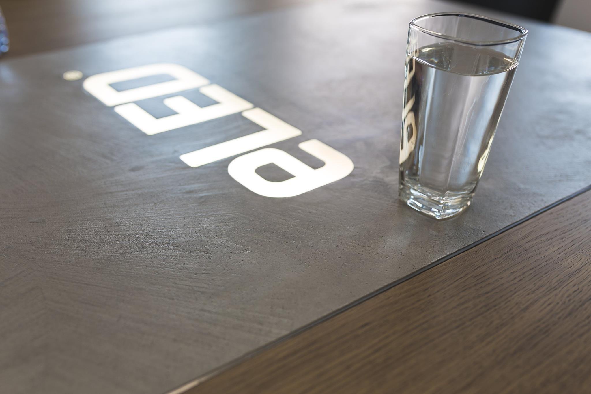 Jedinečný stůl s kombinací betonové stěrky a svíticího loga    -Akce: Atypický designovýstůl  -Autor: Mariana Hendrychováze studia…