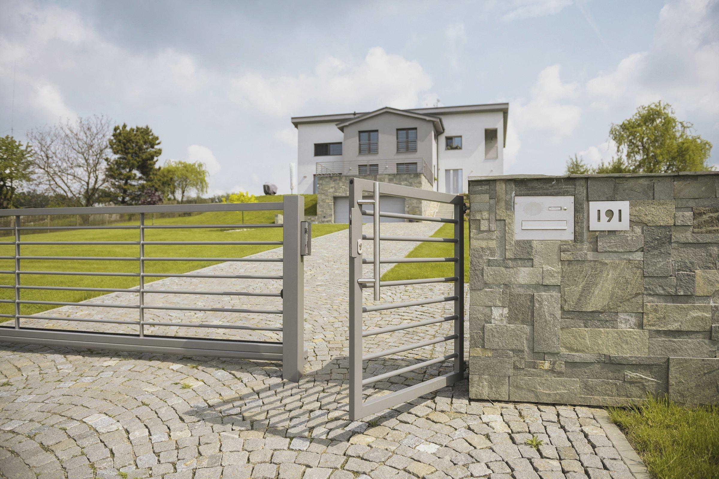 Plot, brána i zábradlí Airy (rodinný dům, Karviná)  Rozlehlý pozemek domu je otevřený. Rámuje jej plotz designové řadyAiry a vjezdu dominuje…