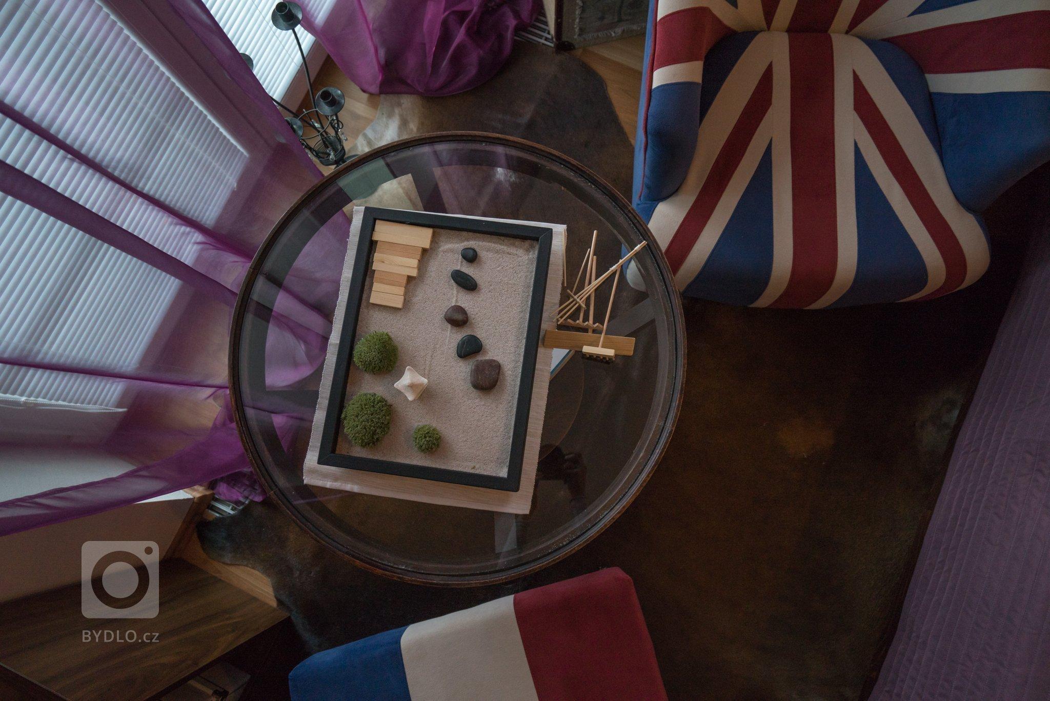 Kufry, trofej, kožešina, křeslo, anglická vlajka, suvenýry ze všech koutu světa. Magická fialová barva. Co víc dodat …