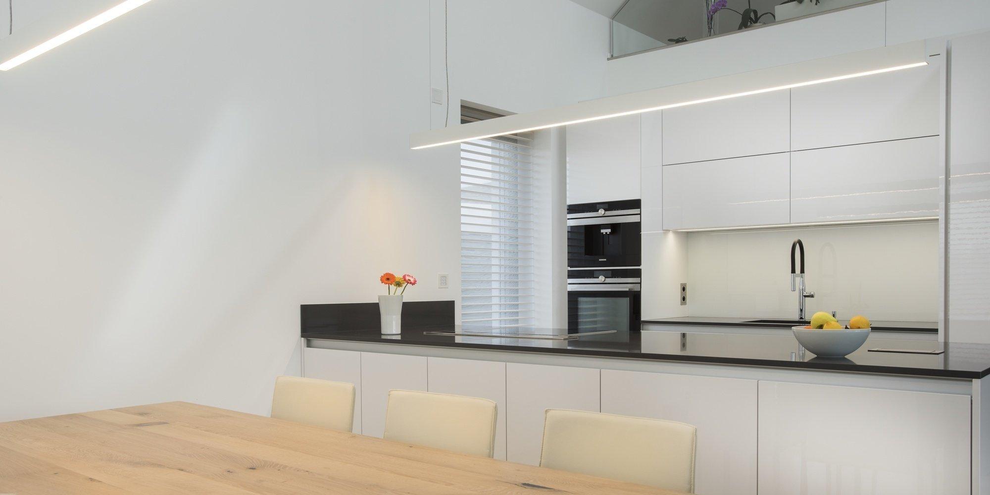 Kuchyň BEECK KÜCHEN, rodinný dům. Provedení - Colora lesk bílá, pracovní deska Technistone Crystal Anthracit. Kuchyň je vybavena spotřebiči Siemens. Stůl a…