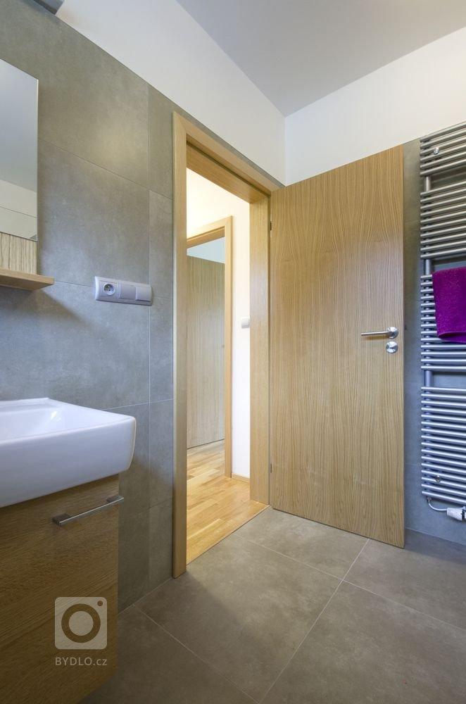 koupelna v barevné kombinaci cementově šedého obkladu a dubové dýhy