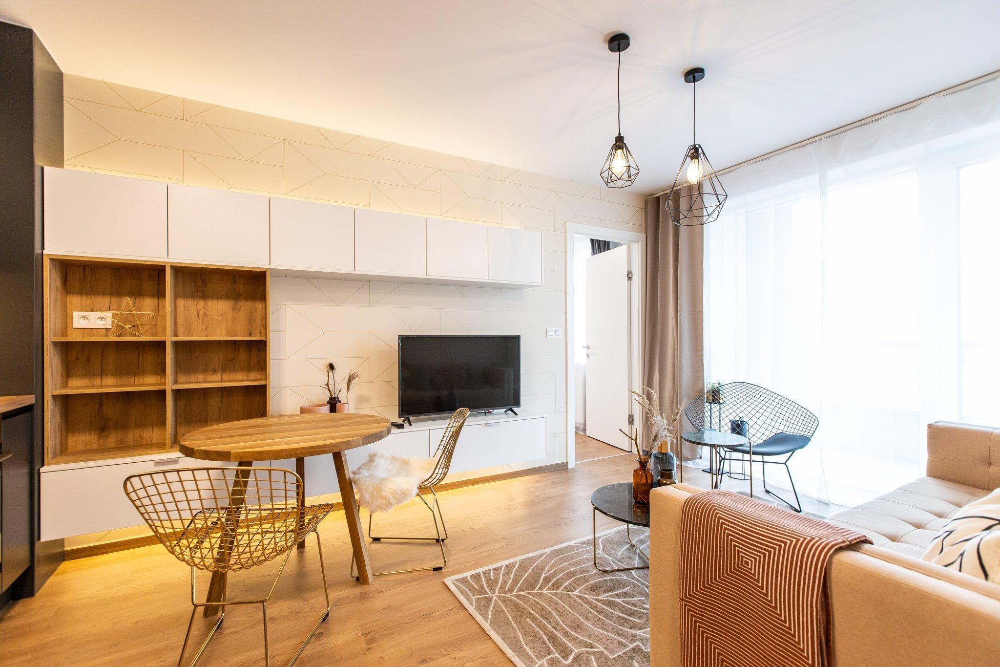 Krásna realizácia, ktorá dokonale prepája antracitovú kuchyňu s bielou obývacou zostavou.