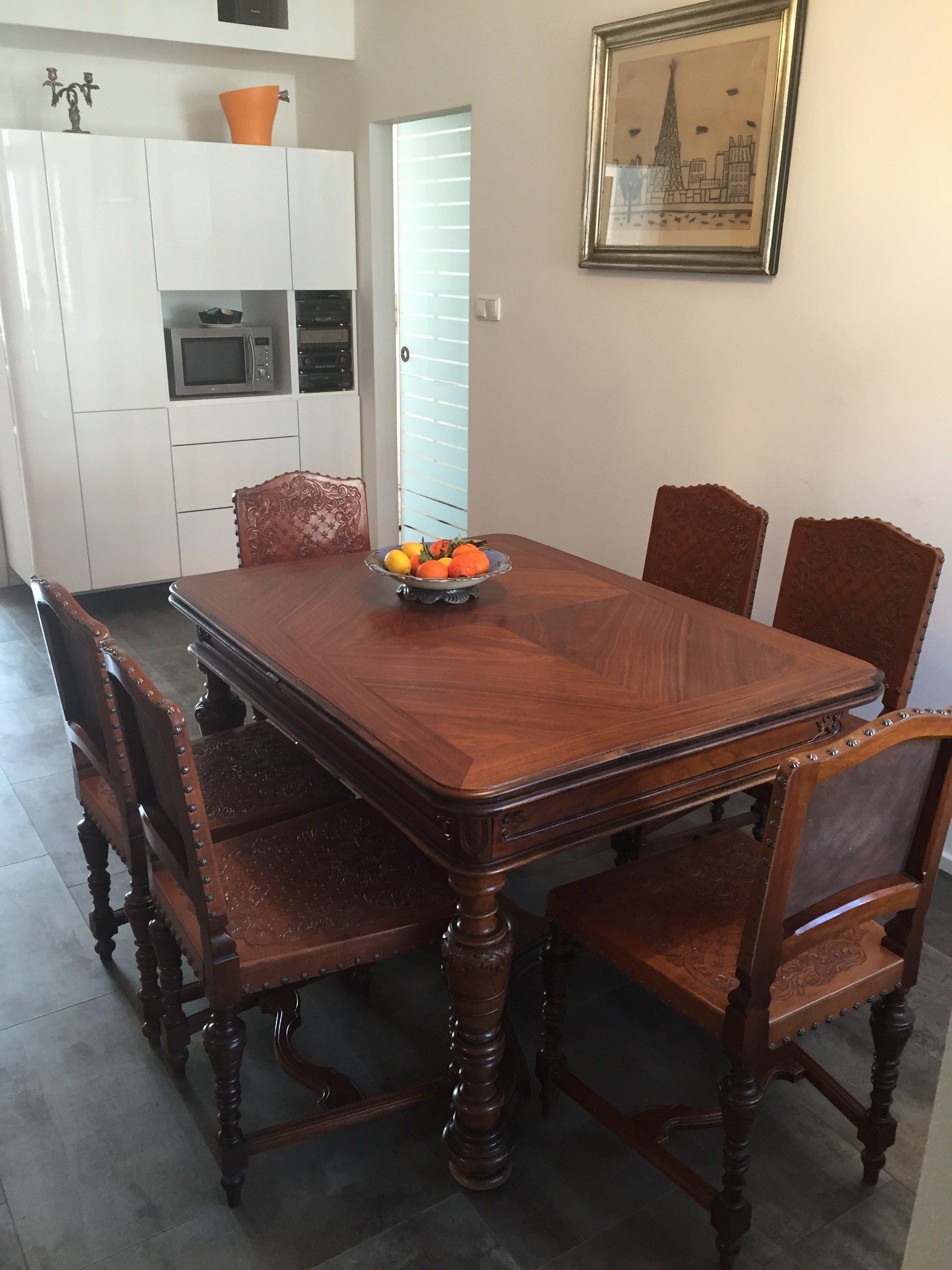 Kuchyňská linka v bílém vysokém lesku doplněná masivní pracovní deskou. V kuchyni je umístěn námi renovovaný starožitný stůl s židlemi a konferenční stolek.