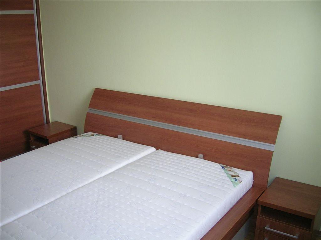 Ložnice s postelí s úložným prostorem, nočními stolky a vestavěnou skříní.