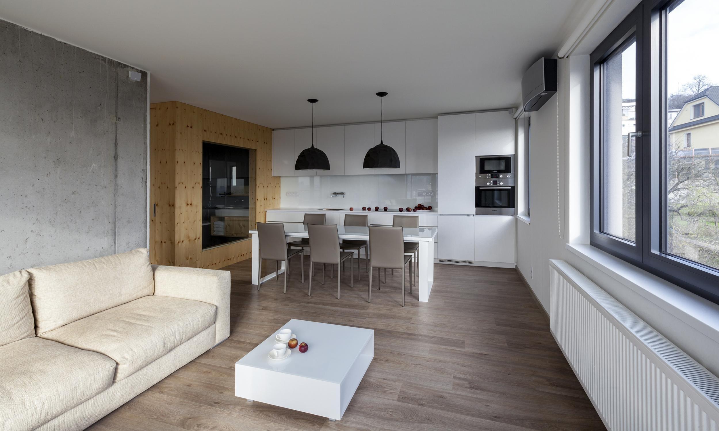 Interiér třípokojového bytu jsme postavili na kontrastu betonu a dřeva. Drsnou přirozenost betonové zdi zjemňuje borovicový kubus s hygienickými prostory. V…