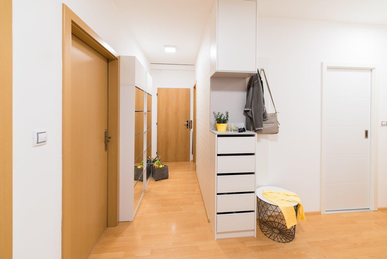 Rodina se 3 dětmi potřebovala zvětšit panelákové úložné prostory v předsíni a celý prostor opticky pročistit. Koupelna stylově navazuje na předsíň, vše v&nbsp…