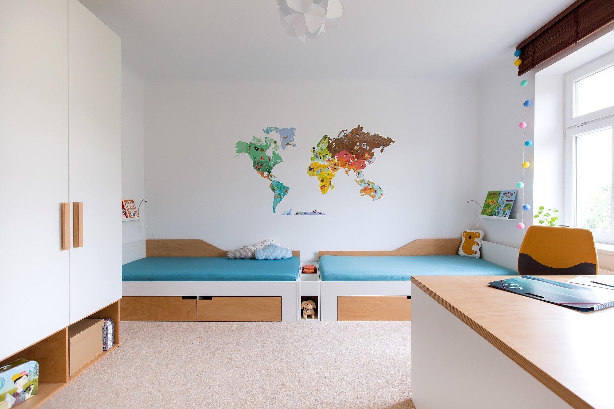 """Veškerý nábytek jsme navrhly na míru vkombinaci bílého lamina spřekližkou.  Skříň """"stojí"""" na otevřených překližkových boxech, které…"""