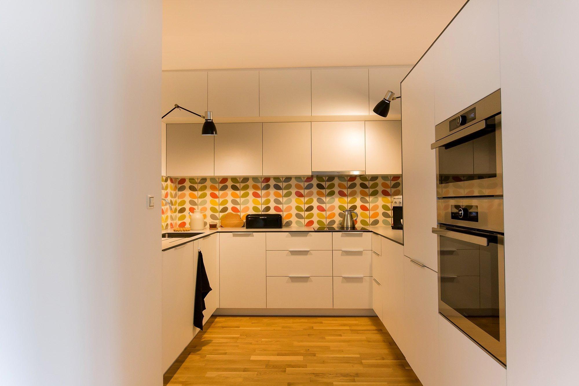 Koncept byl jasný- jednoduchá světlá linka vyladěná tapetou od Orly Kiely, která celý prostor rozzáří. Kuchyň se nachází vtmavém koutě bez okna, proto je…