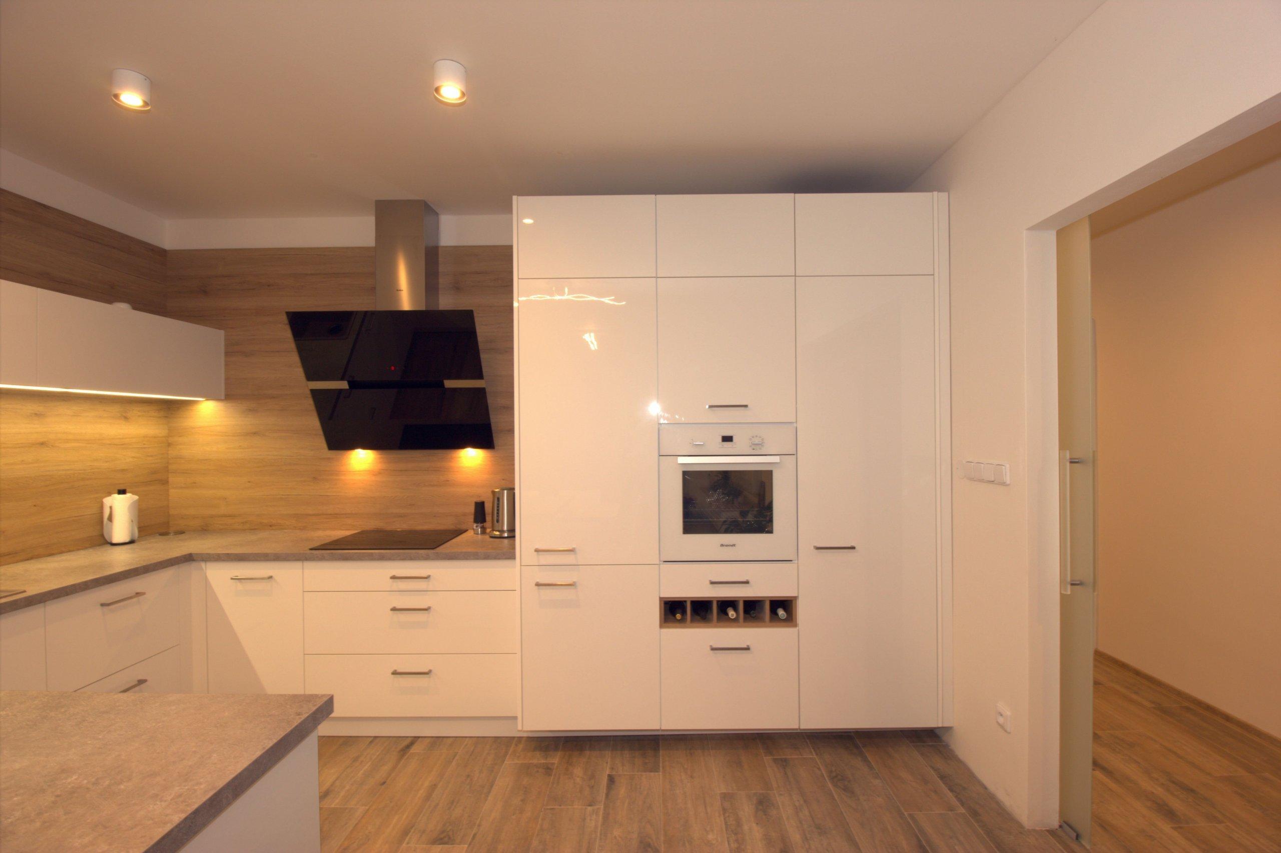 Bílá kuchyň doplněná přírodním dubem.