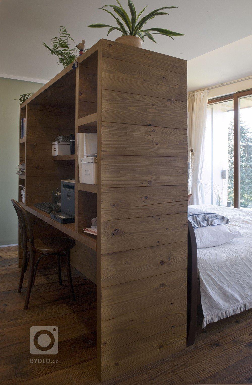 Dělící stěna mezi postelí a pracovnou je současně obostrnnou knihovničkou či nočním stolkem