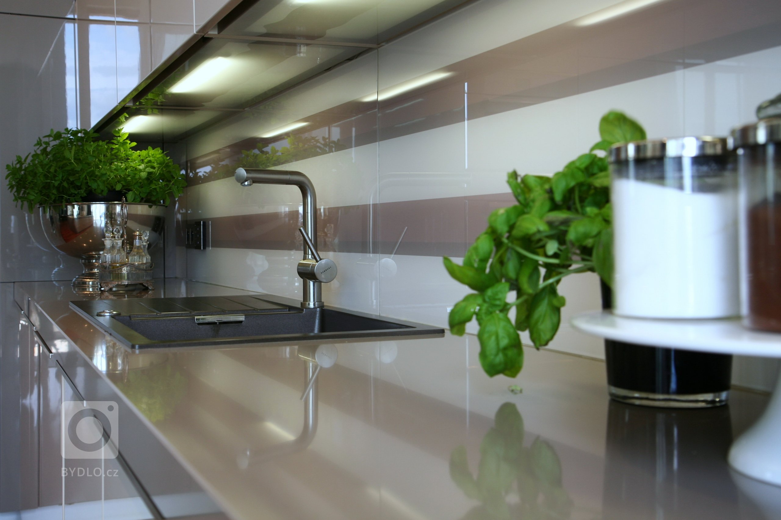 Kuchyně SCHÜLLER GALA -Sestava ve vysokoleském laku, ostrůvek s varným centrem, pracovní desky z technického kamene. Spotřebiče značky De Dietrich a…
