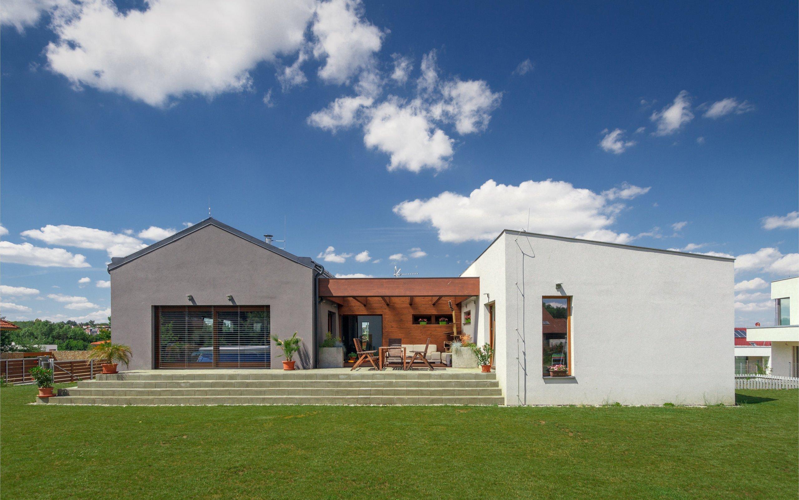 Dům je umístěn v severní části pozemku a otevírá se velkým francouzským oknem a atriem na jih do zahrady. Svou formou - tvarem střech a velikostí hmot -…