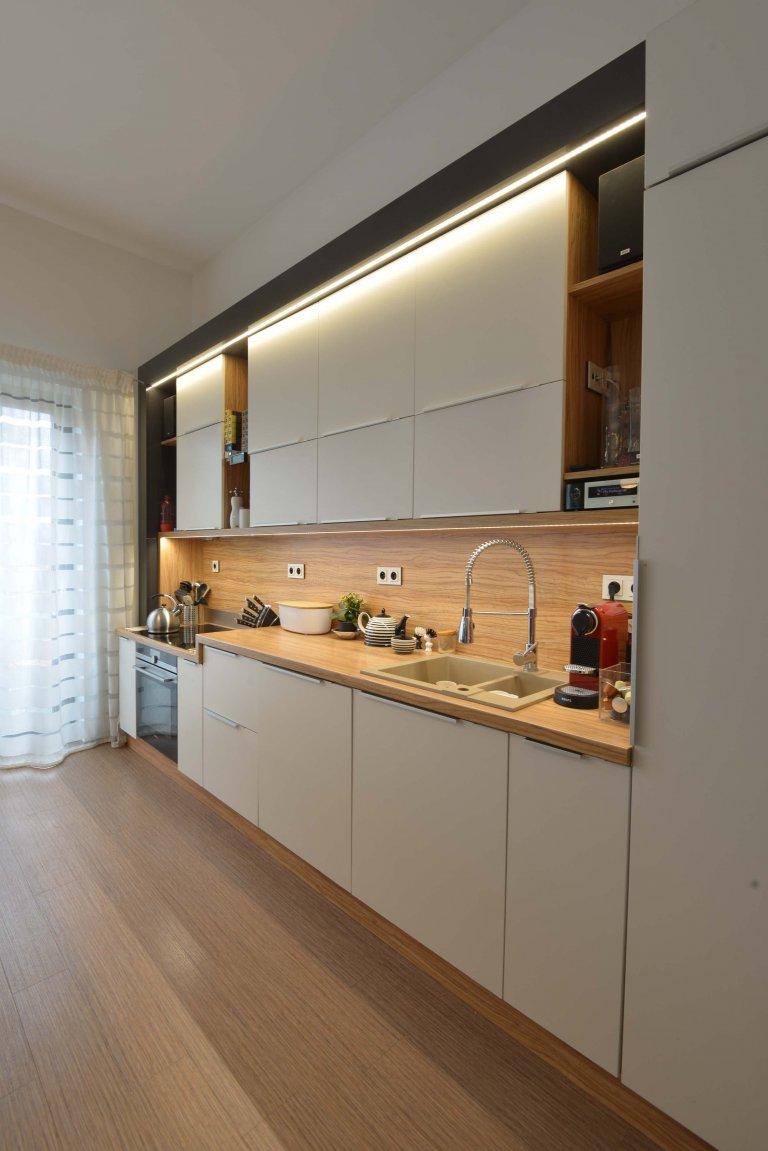 Boční pohled na kuchyň. Kuchyň je osazená v antracitovém lesklém rámu se zabudovaným osvětlením LED a má sníženou varnou zónu.