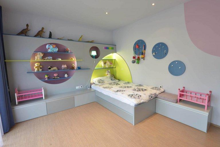 Pohled na dělanou postel s úložným prostorem. Pokoji vévodí předstěna s kulatými a půlkulatými výřezy na odkládání hraček. Vše se zabudovaným osvětlením LED.