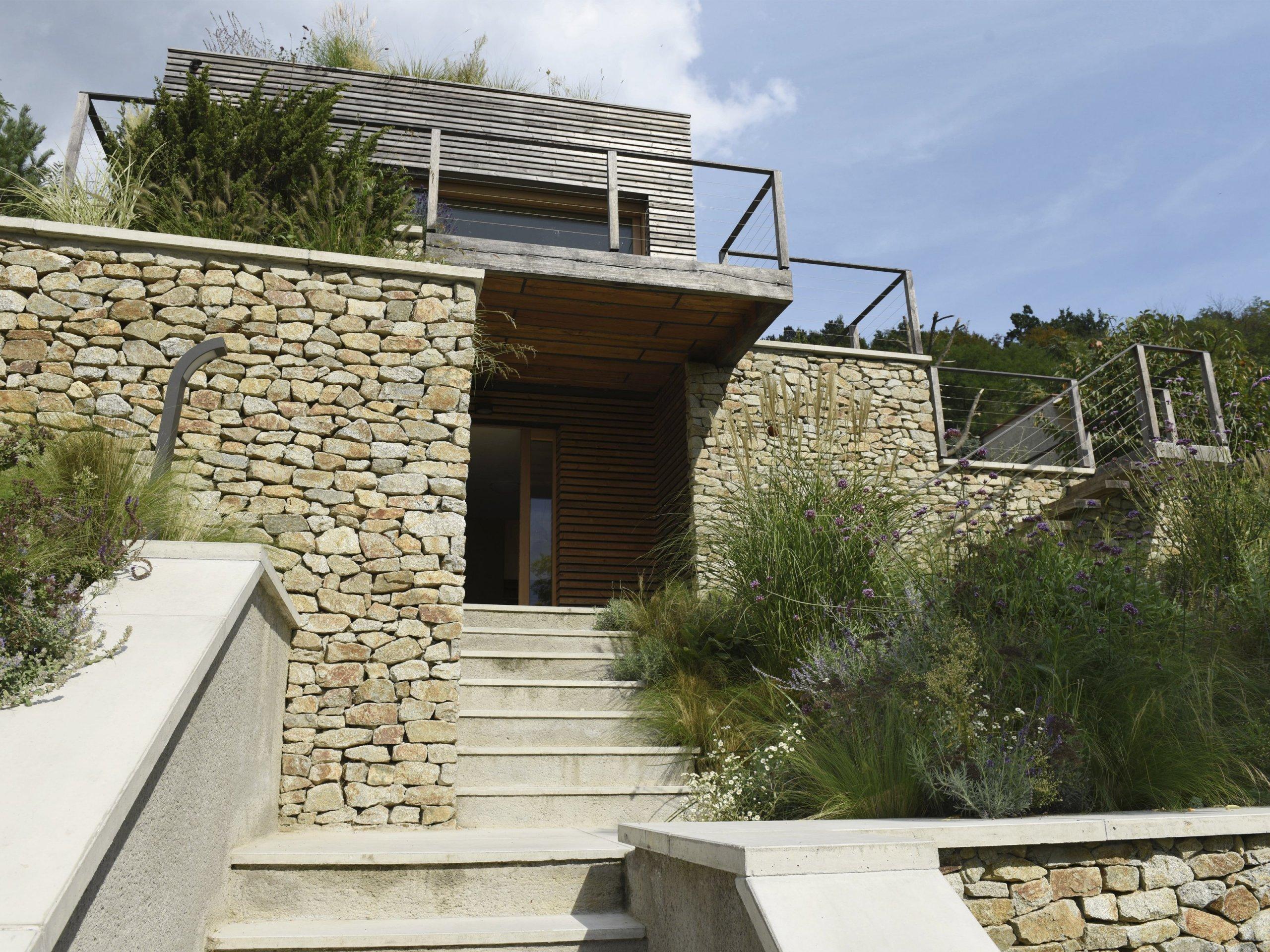 Úzká a svažitá parcela predurčila formu tohoto domu. Práce s terénem a ambice splynout s okolním prostředím jsou charakteristickými rysy prezentovaného díla.