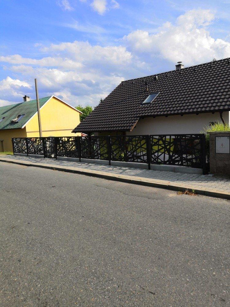 Domek v Čáslavi se zahrádkou a designovým plotem.