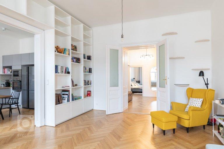 obývací pokoj s knihovnou a žlutým ušákem