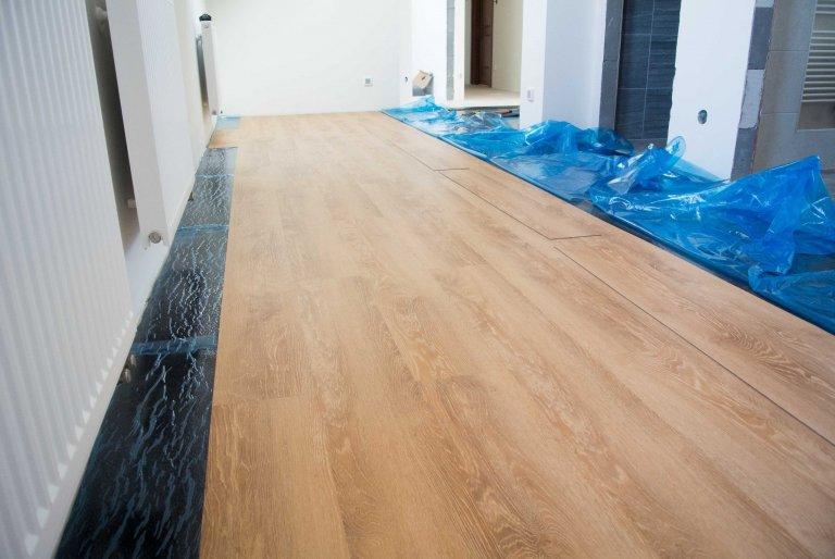 Následně se ze samolepicí vrstvy odstraňuje fólie a pokládá se vinylová podlaha