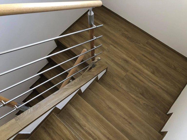 Schodiště s vinylovou podlahou BUKOMA PREMIUM CLICK Dub Gladstone Hnědý. Stejný dekor jako na podlaze je i na téměř všech plochách v domě, položeno bez…