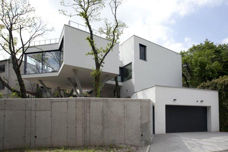 Z pohledu ulice se dům snaží nepoutá pozornost, což se mu díky neutrálním materiálem a velkému množství zeleně i podařilo.