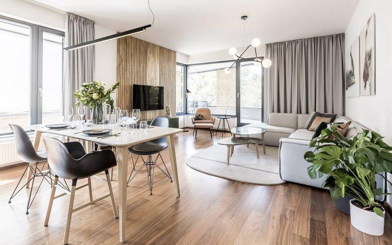 Obývací pokoj v šedých tónech v kombinaci se dřevem.
