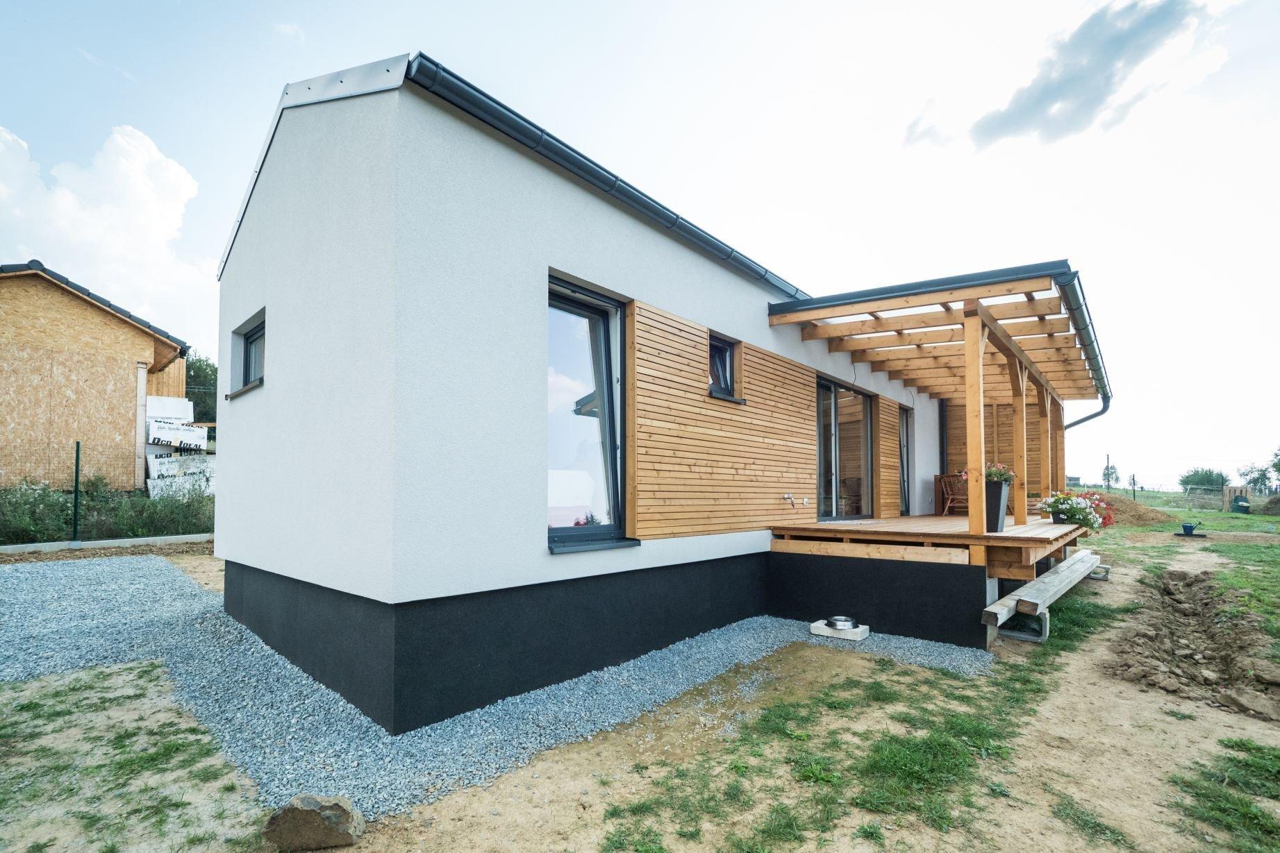 Dřevostavba EASY 48 s terasou a pergolou dokončená letos v létě. Kombinace bílé fasády, antracitové střechy a oken a obkladu ze sibiřského modřínu s…