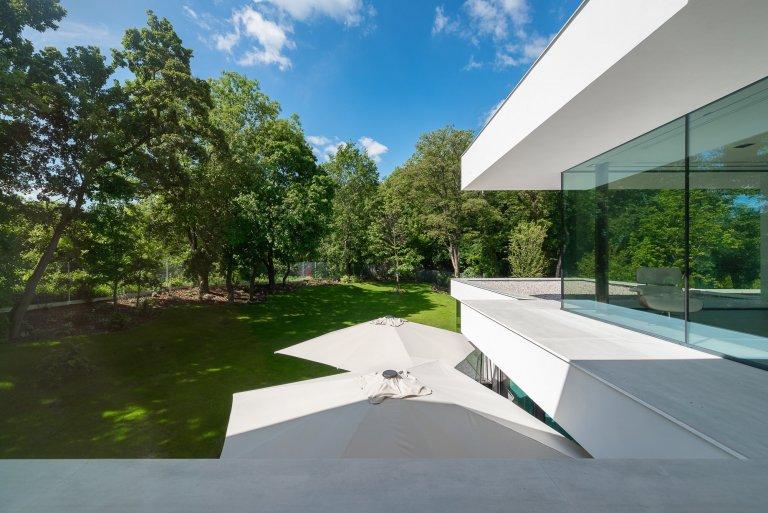 Velkorysé prosklení čelní strany domu ačistě bílá konstrukce odkazující se kfunkcionalismu - to jsou hlavní rysy vily vpražských Kolodějích.…