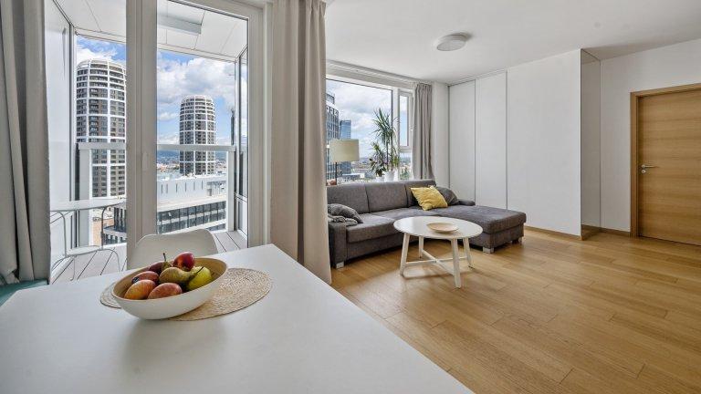 Realizace bytu v Panorama City v Bratislavě. Světlý dekor nábytkuprolnutý dubovými prvkya nadčasovým designem vytváří koncpet…