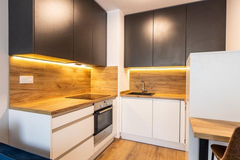 Krásne minimalisticky zariadený byt v Urban Residence, ktorého dominantou je modrá rohová sedačka. Kuchynská linka je krásne ladená v tónoch ceého bytu, aby…