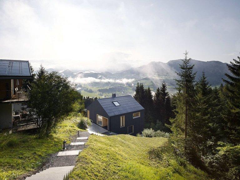 Černě oděný víkendový dům u lesa
