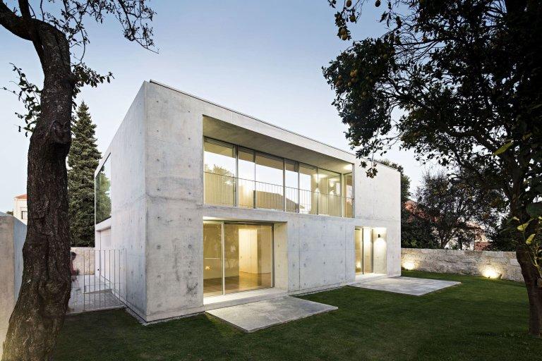 Monolitický betonový kvádr narušují pouze velké prosklené otvory, které propojují obytnou část domu se zahradou