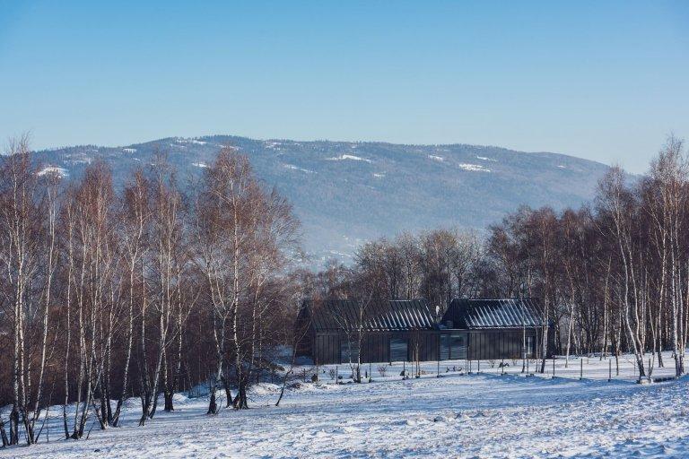 V malebné krajině Slezských Beskyd byl do svahu posazen moderní dům, který se stal originálním venkovským sídlem pro pětičlennou rodinu. Z části je zapuštěn do země, a tak od příjezdové cesty ukazuje jen svou horní polovinu s tradiční sedlovou střechou. Z pohodlí domova prohřátého teplem krbu poskytuje úchvatné výhledy do zasněženého okolí.