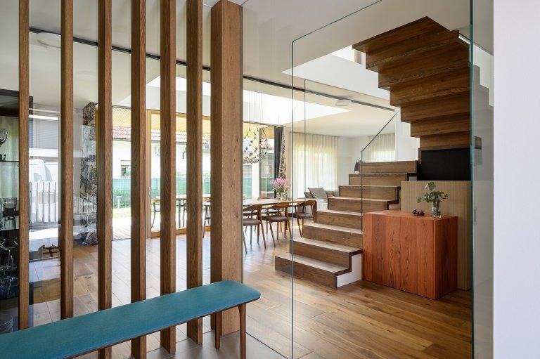 Hlavní roli v čerstvě dokončeném interiéru domu ve Slovinsku hraje dřevo.  Představuje hned několik odstínů a kreseb, stará se o dynamiku prostoru a příjemně prohřívá poněkud chladnou bílou výmalbu. Naproti mu přicházejí svěží akcenty lososové barvy, které jsou decentním osvěžením tohoto originálně pojatého interiéru.