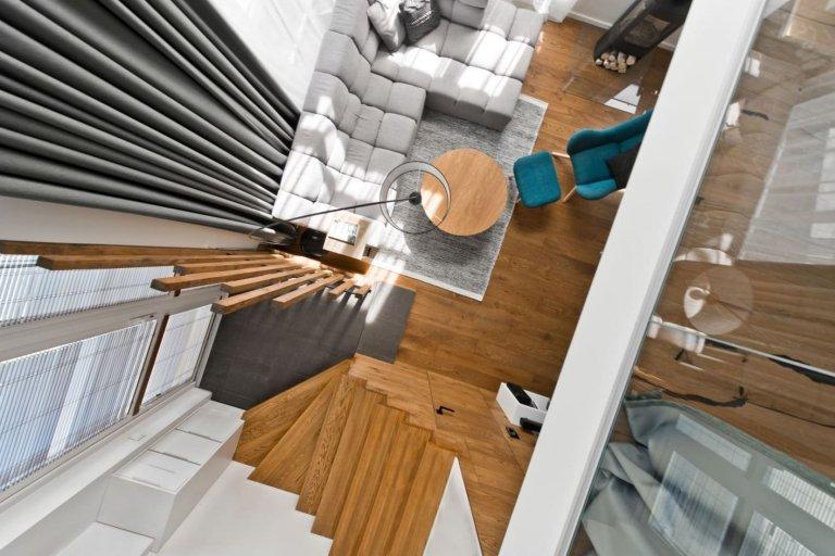 Moderně zařízený loftový byt se stal domovem mladého páru, který miluje kombinaci dřeva a teplých barev. Na první pohled v něm zaujmou horní kuchyňské skříňky připomínající svým seskupením tvar harmoniky. Zajímavým opakujícím se prvkem v interiéru jsou také subtilní dřevěné laťky doplněné o LED pásky, které jakoby představovaly světelné paprsky.