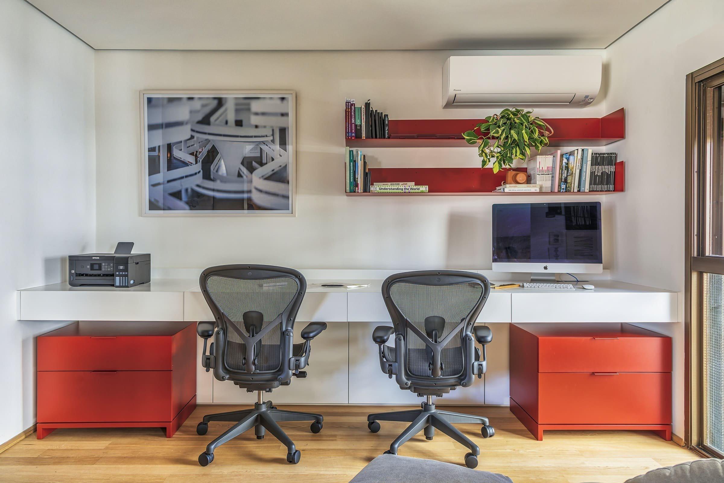 Bílé stěny a dřevěnou podlahu oživuje červená barva nábytku