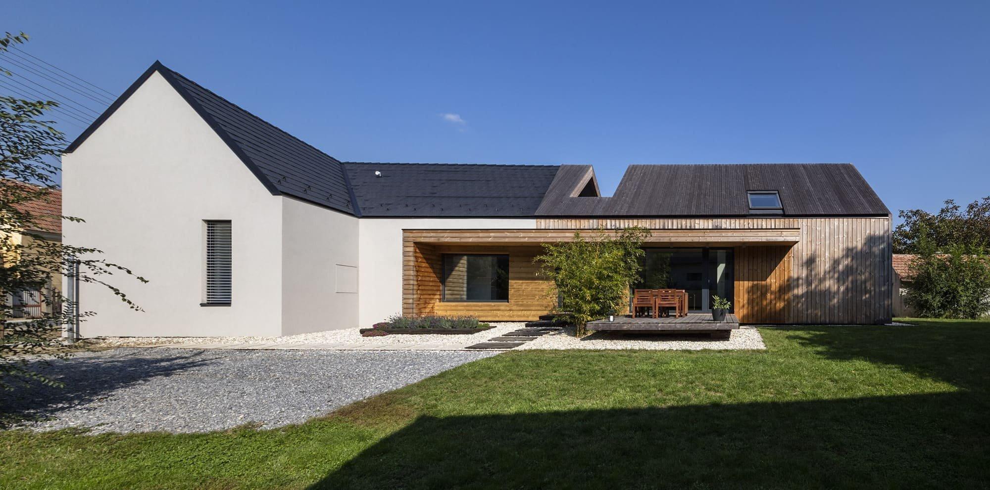 Nová část stavení má velká okna, která propojuje interiér se zahradou