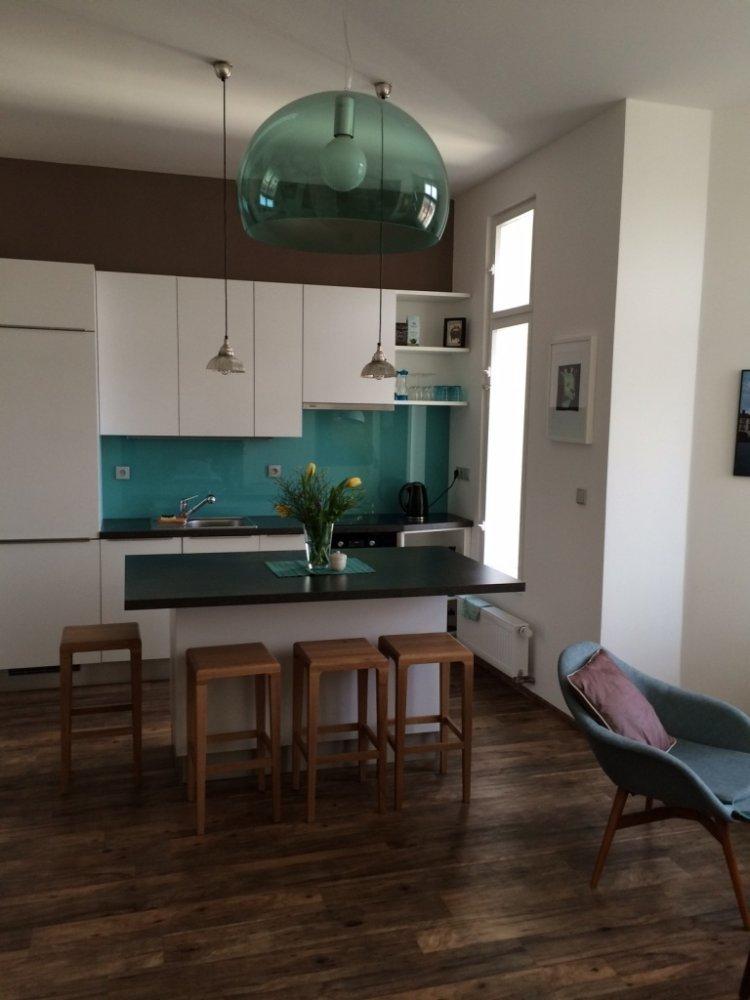 Malá bílá kuchyně s tyrkysovým sklem