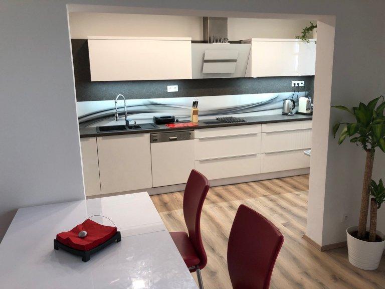 kuchyňská linka ve vysokém bílém lesku s grafosklem