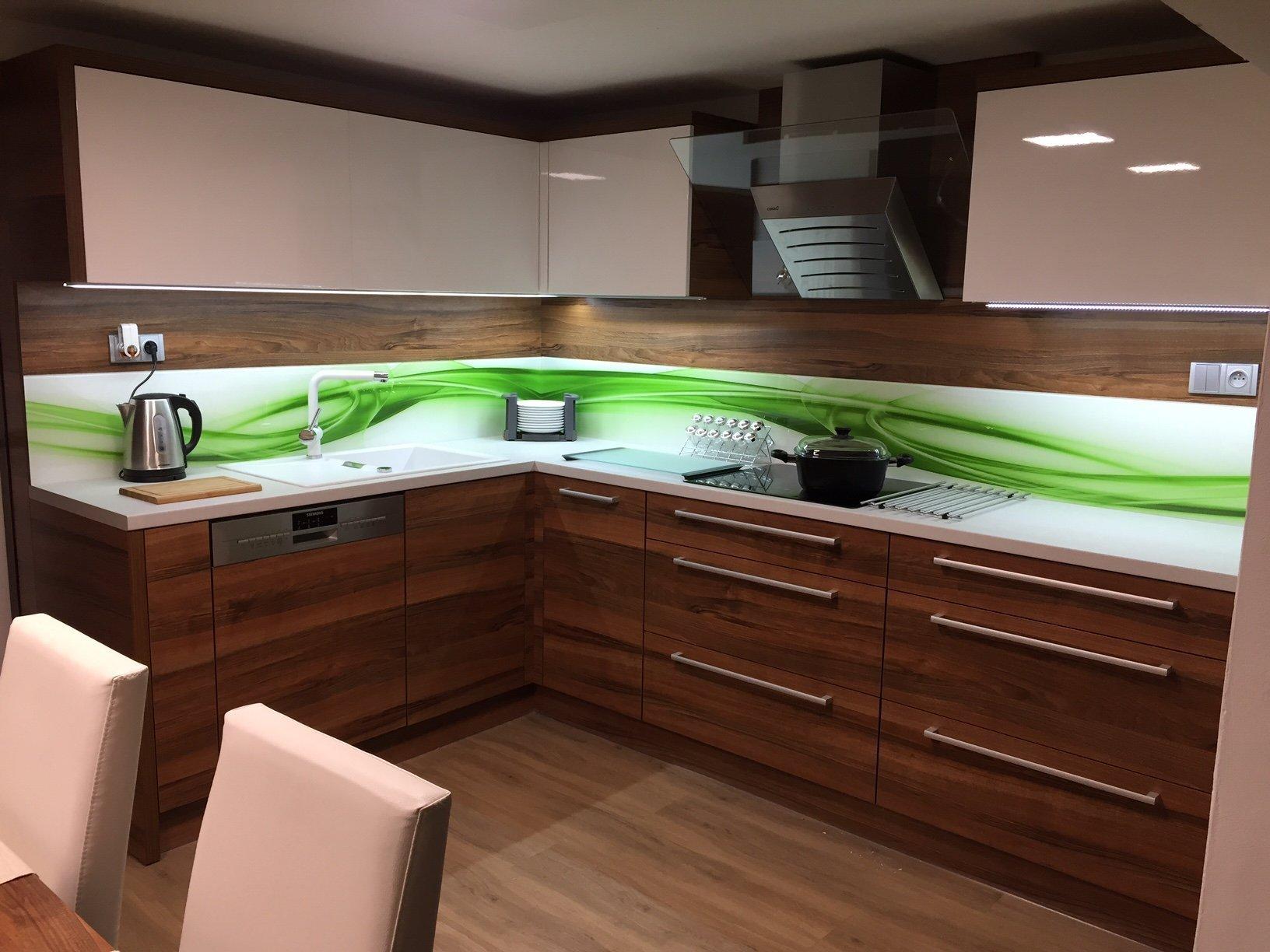 Kuchyňská linka v ořechovém provedení v kombinaci s vysokým bílým leskem doplněná o designové grafosklo s motivem zelené vlny. Místnost doplňuje jídelní stůl s…