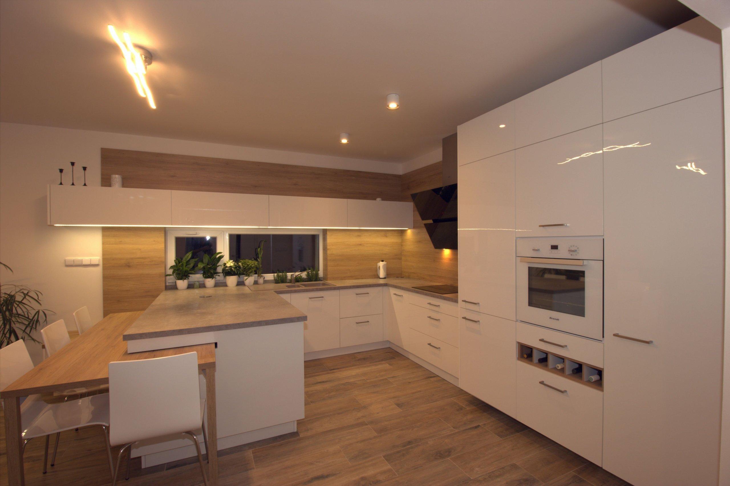 Vize klientky byla jasná, kuchyň svysokým dřevěným obkladem a vybíhající horní bílá skříňka.  Kuchyně je ve tvaru U a na ní navazující stůl. Stůl je…