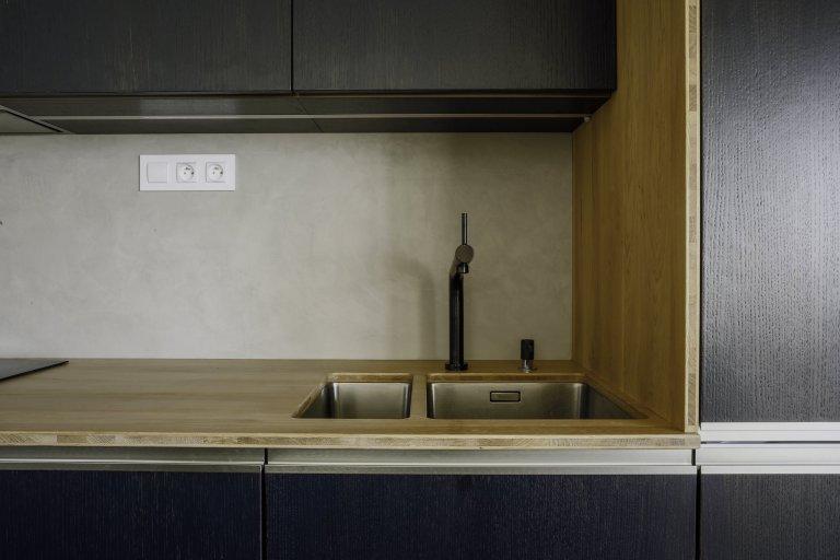 Odvážná kuchyně v novostavbě, kdy je tmavá barva zjemněná dubovou bio deskou a kresba dřeva pod dýhovaným mořeným dvířkem krásně prostupuje a vytváří zajímavý…