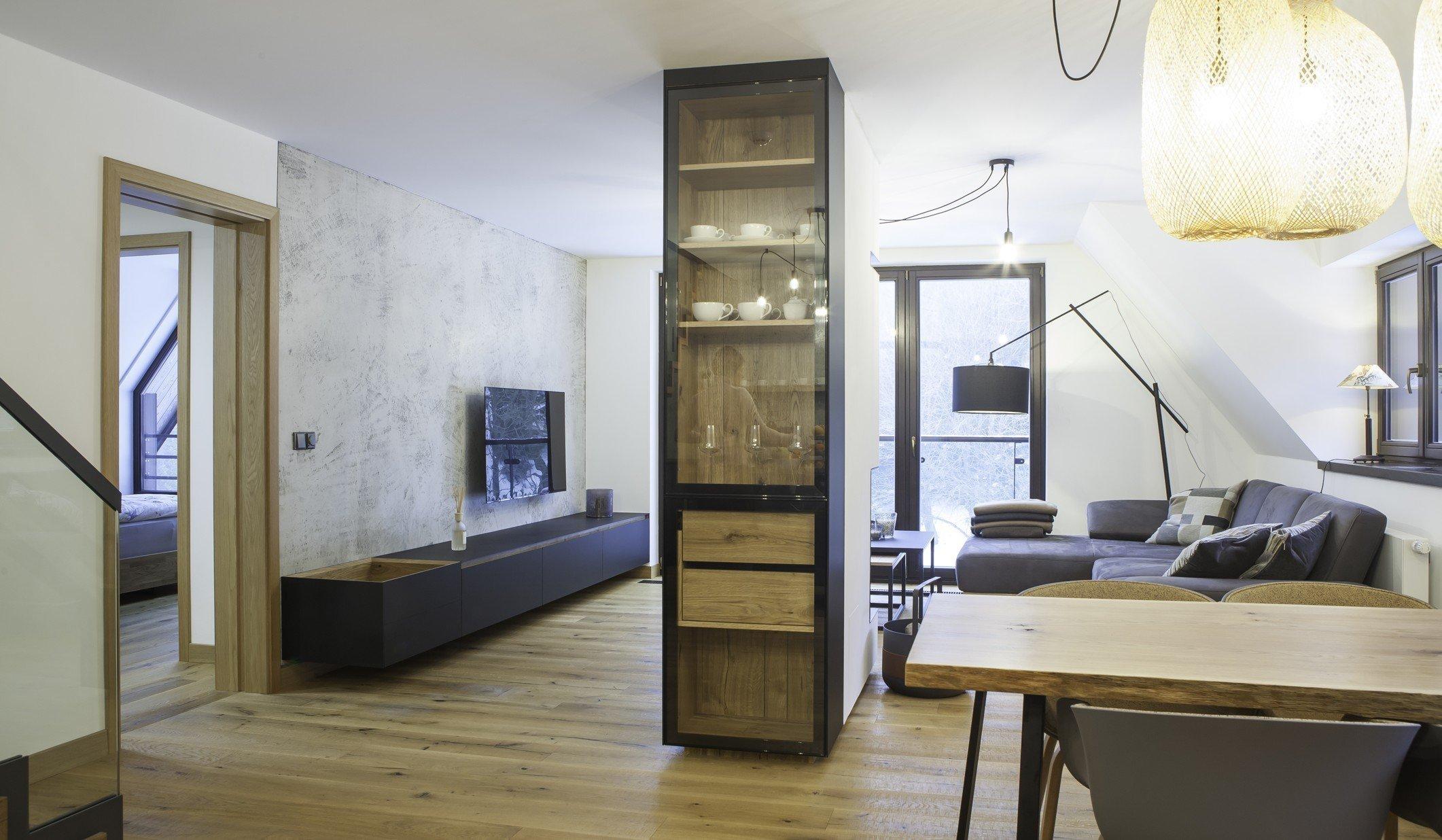 Ložnice rodičů a koupelna tvoří velkorysý prostor s minimem nábytku. Koupelna je od ložnice oddělená skleněnou stěnou.  V kuchyni matná šedá a černá příjemně…