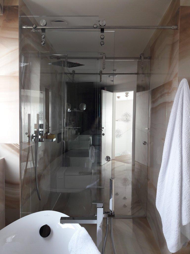 Koupelna se skleněnými dělícími stěnami.