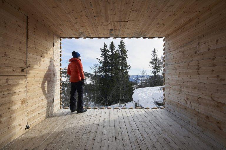 Chata zabalená plotem odolává drsným podmínkám na vrcholku hory