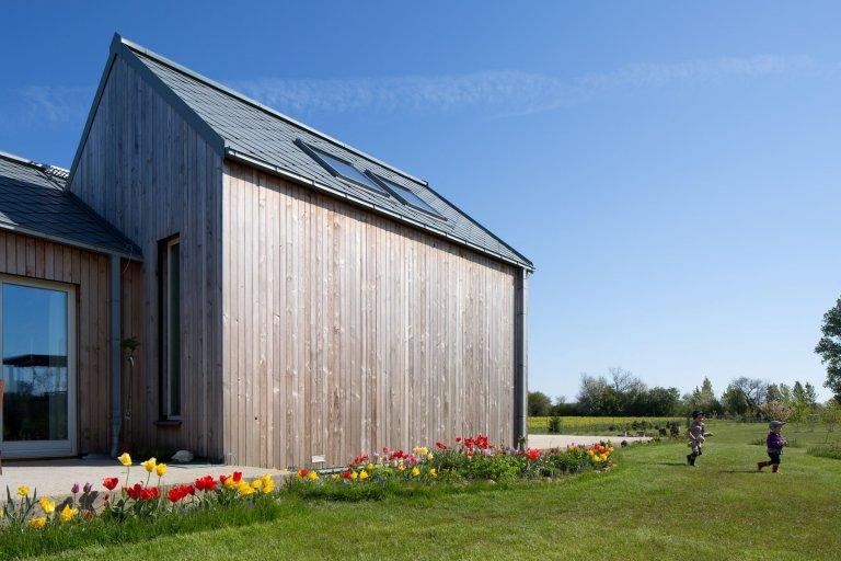Jednoduchý, ale velký dům se sedlovou střechou, obložený dřevěnými prkny, okny s výhledem na zahradu a okolní přírodu - takhle vypadá dům snů pro manželský pár v důchodu.