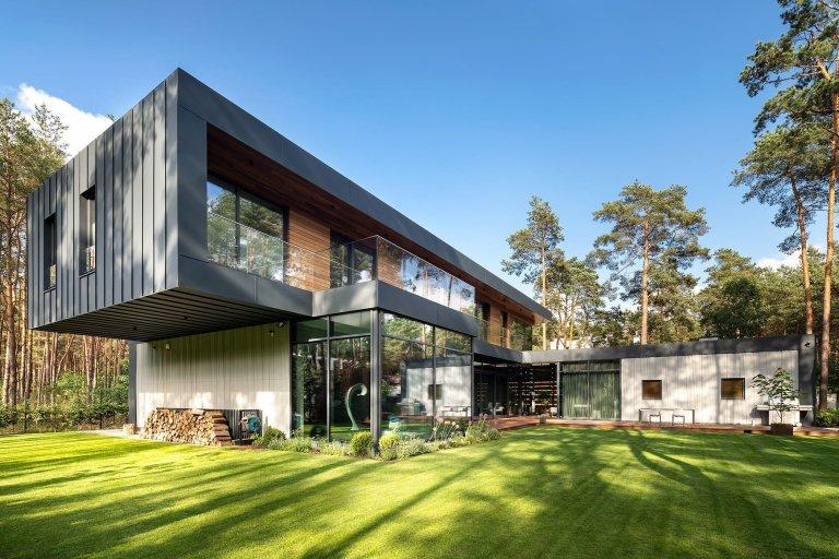 Dům s betonovou fasádou obklopený lesy