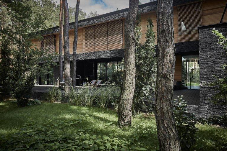 Dům s fasádou z břidlice uprostřed lesa
