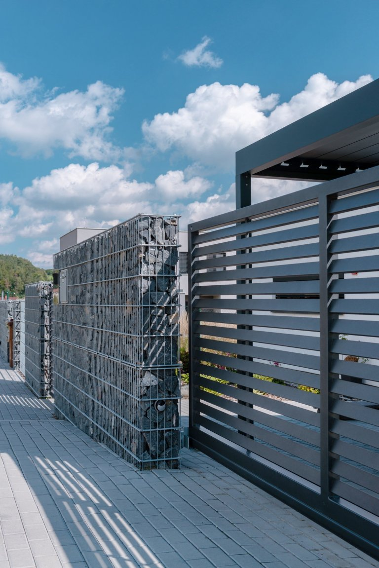 K modernímu domu, moderní plot (rodinný dům, Ostrava)  Klient si přál, aby plot zajišťoval soukromí a zaclonil hlavně příjezdovou část, poněvadž dům je pod…