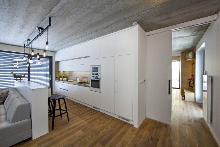 V celém domě se prolínají přírodní materiály s černými kovovými prvky a detaily s bílými stěnami a dveřmi. Industriální ráz podtrhují přiznané betonové stropy…